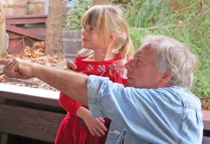 Grandpa Chuck pointing something out to Rylin while waiting to get on the train at Silver Dollar City.