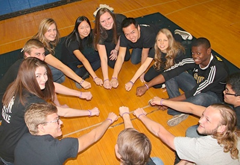 """After a brief rehearsal for their upcoming performance at Olathe South, B.R.A.V.E. members showed off the group's wristbands which they distribute as a symbolic reminder that students are joining the chain reaction to stand up and speak out against bullying and violence. """"Those directly involved in B.R.A.V.E. are making a difference and they know it,"""" Principal Phil Clark said. Photo by Marlene Colgan"""