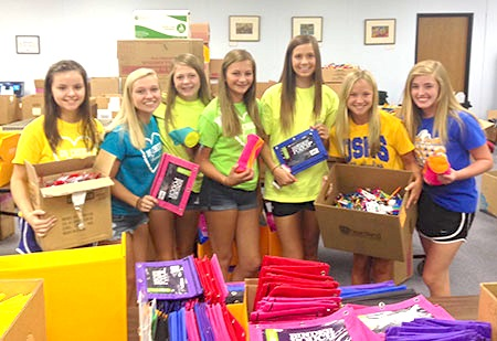 Olathe South High School cheerleaders spent time opening large packages of supplies so volunteers from Farmers Insurance could more easily get the right number of each item into the backpacks.